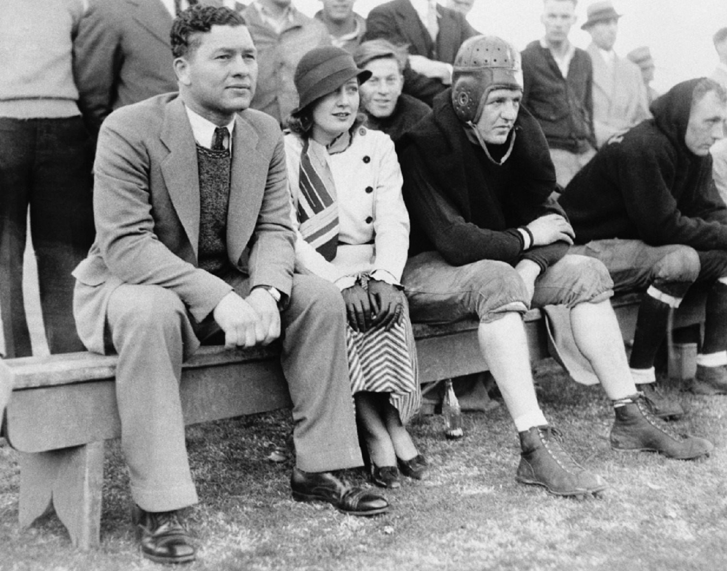 Packers Head Coach Curly Lambeau sits with actress Myrna Kennedy and Chicago Bears icon Red Grange at an all-star game in 1933.<br />