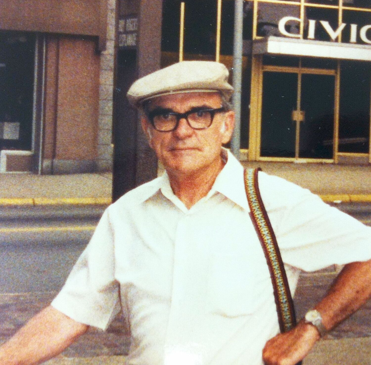 Carl Ackerman with camera strapped over his shoulder, standing on the Esplanade, at the intersection of Chillicothe and Gallia Streets, Portsmouth, Ohio, c. 1980.